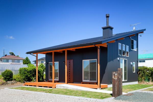 При облицовке односкатного дома темным металлом, его сочетают со светлым деревом